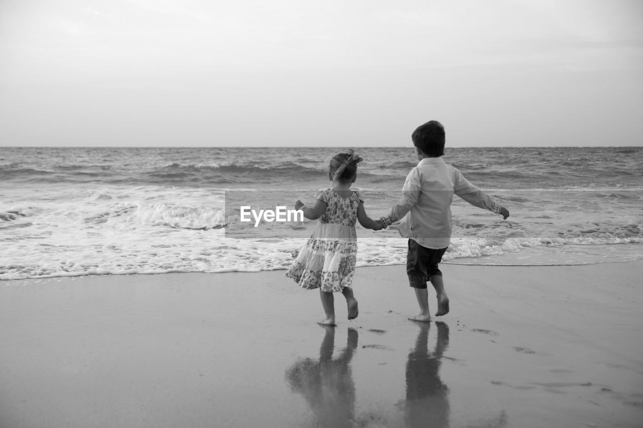 sea, beach, real people, horizon over water, sand, shore, childhood, water, two people, boys, walking, full length, nature, togetherness, leisure activity, rear view, vacations, standing, lifestyles, sky, outdoors, day, ankle deep in water, scenics, beauty in nature, bonding, wave, people