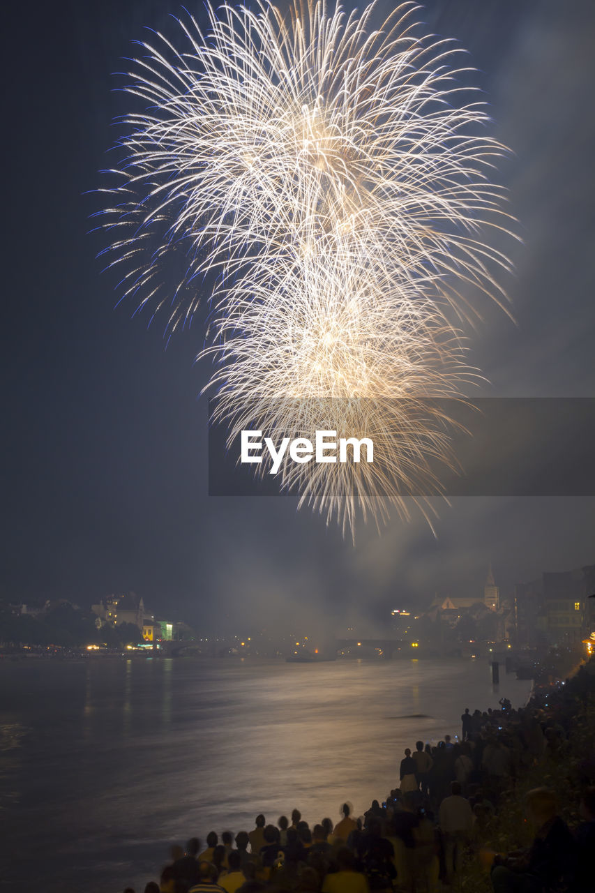 illuminated, firework, firework display, night, arts culture and entertainment, motion, exploding, celebration, event, sky, nature, building exterior, long exposure, glowing, architecture, water, firework - man made object, built structure, no people, outdoors, light, cityscape, sparks