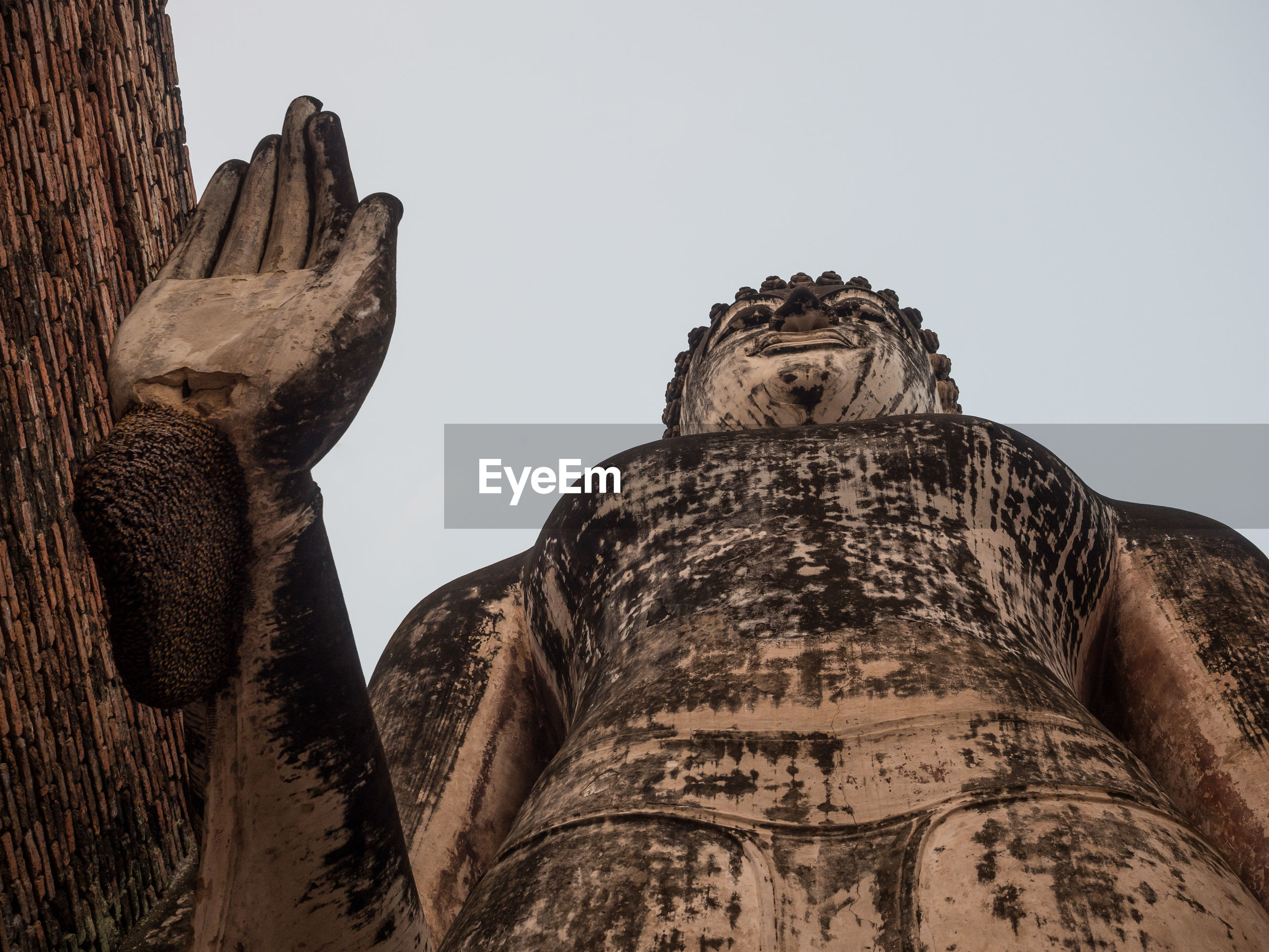 Low angle view of buddha statue at sukhothai historical park, thailand