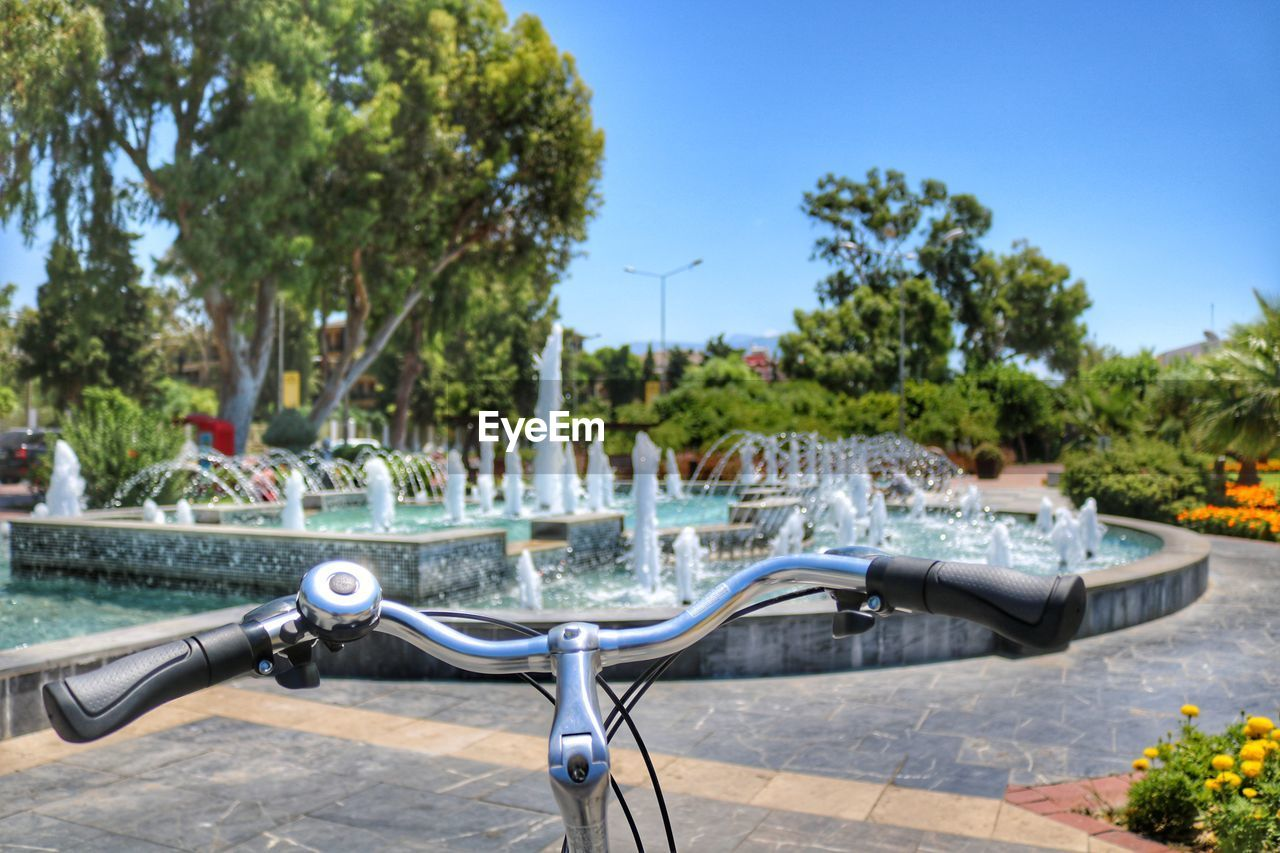 Close-Up Of Bicycle By Fountain Against Sky