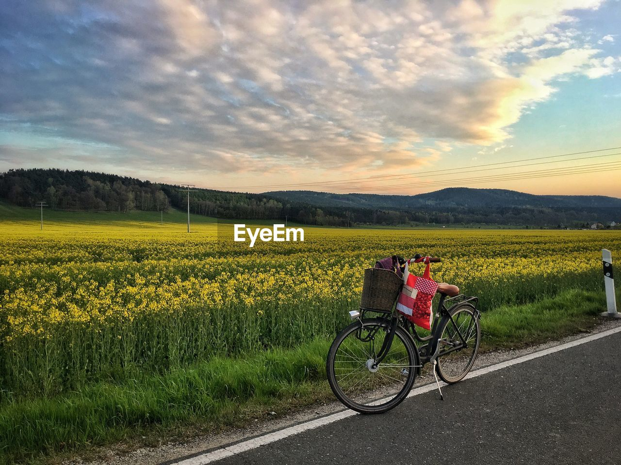 Bicycle On Agricultural Field Against Sky During Sunset