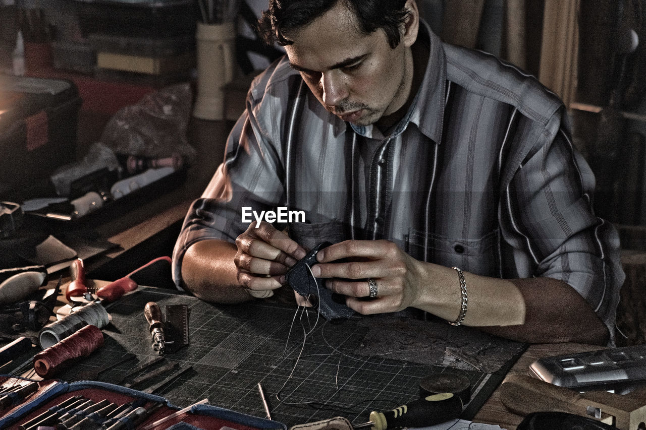 Man working with leather at table in workshop