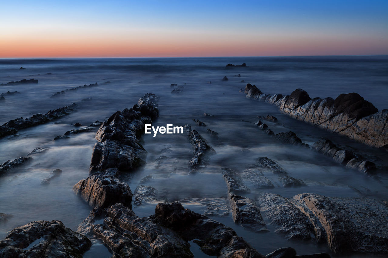 Blurred motion of sea over rocks during sunset