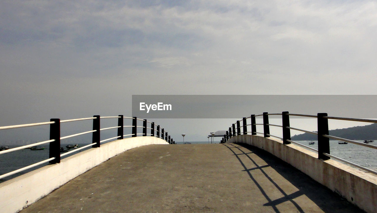 railing, sky, water, sea, nature, the way forward, built structure, architecture, cloud - sky, direction, bridge, day, no people, pier, connection, outdoors, beauty in nature, tranquility, scenics - nature, diminishing perspective, bridge - man made structure, long, balustrade, promenade