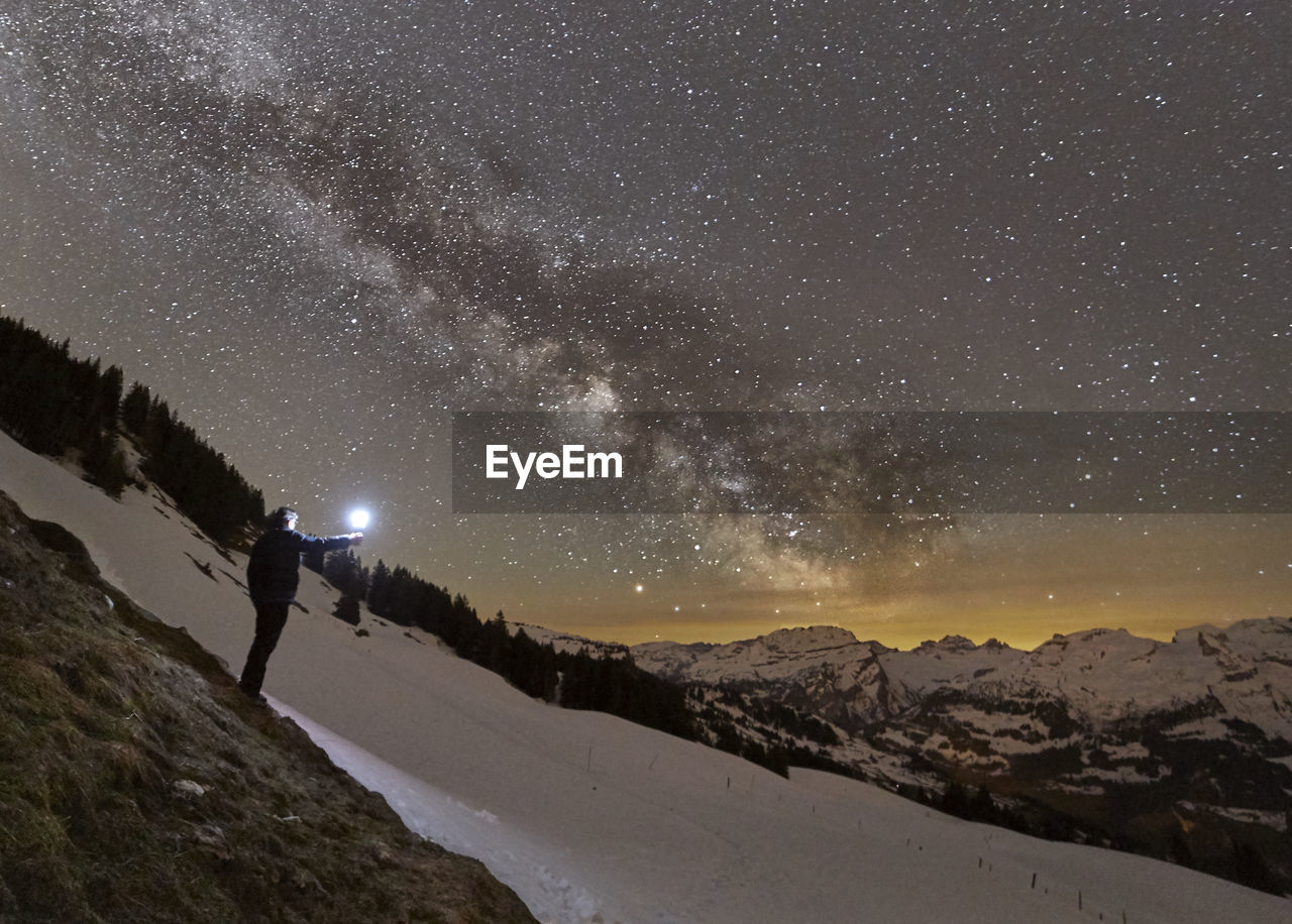 Man With Flashlight Standing Against Star Field On Snowcapped Mountain