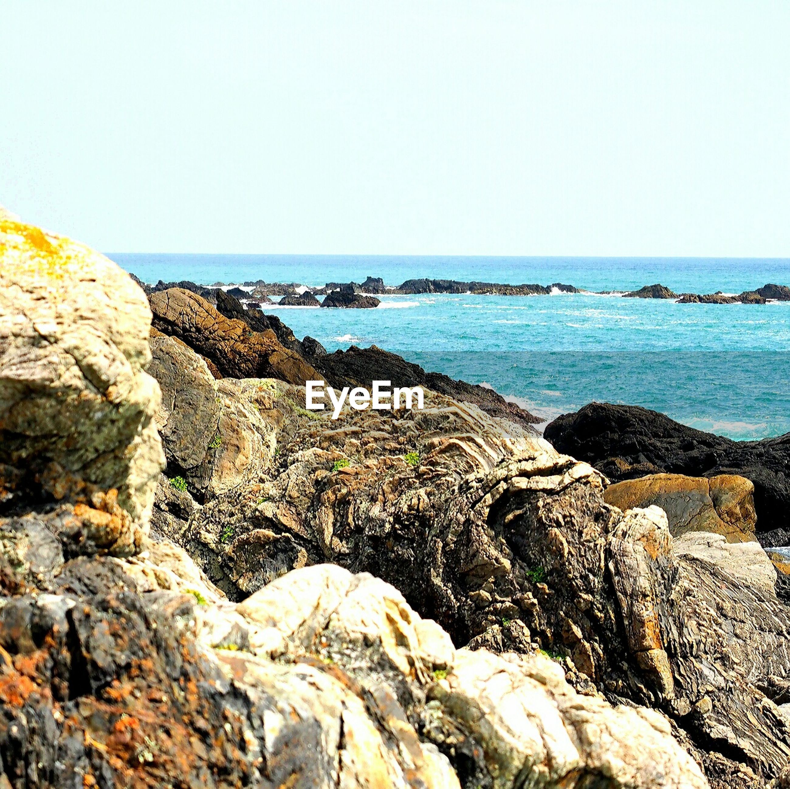 sea, horizon over water, water, clear sky, scenics, beauty in nature, rock - object, tranquil scene, tranquility, rock formation, nature, copy space, rock, beach, shore, idyllic, cliff, blue, outdoors, rocky