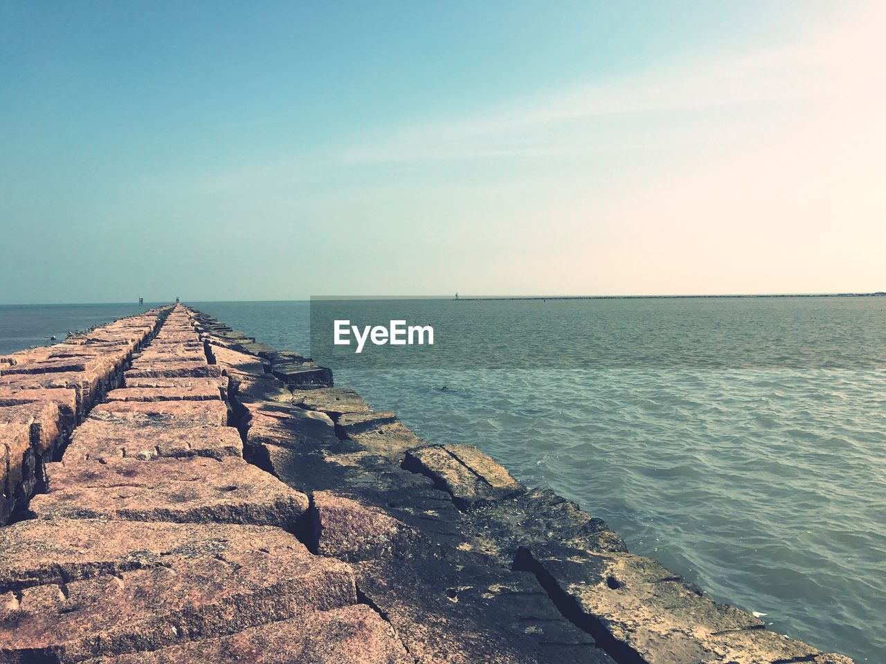 sea, water, horizon over water, tranquil scene, tranquility, scenics, nature, beauty in nature, clear sky, outdoors, day, rock - object, sky, no people, groyne