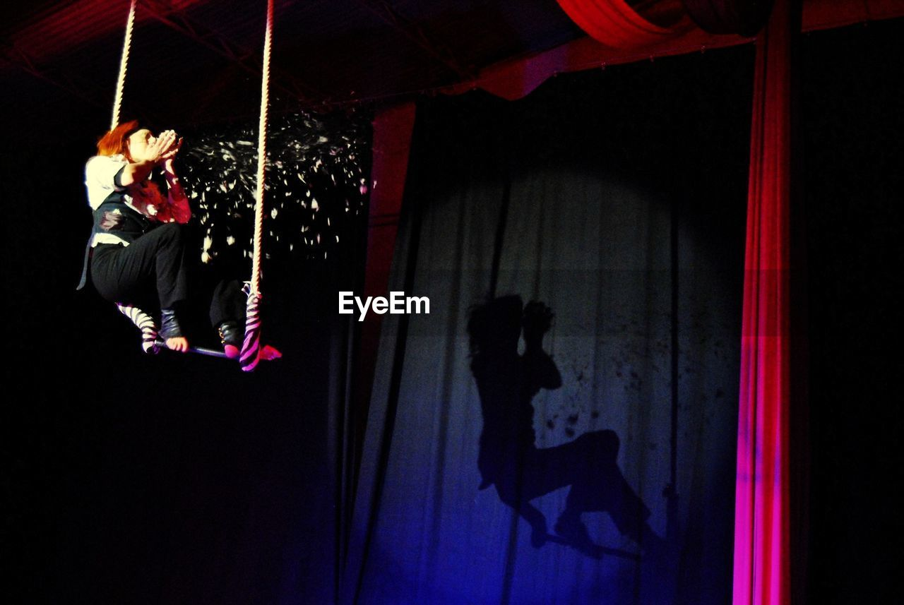 real people, people, full length, indoors, performance, lighting equipment, leisure activity, lifestyles, hanging, arts culture and entertainment, illuminated, circus, night, sport, acrobat, skill, dancing, stage, men, dark, light