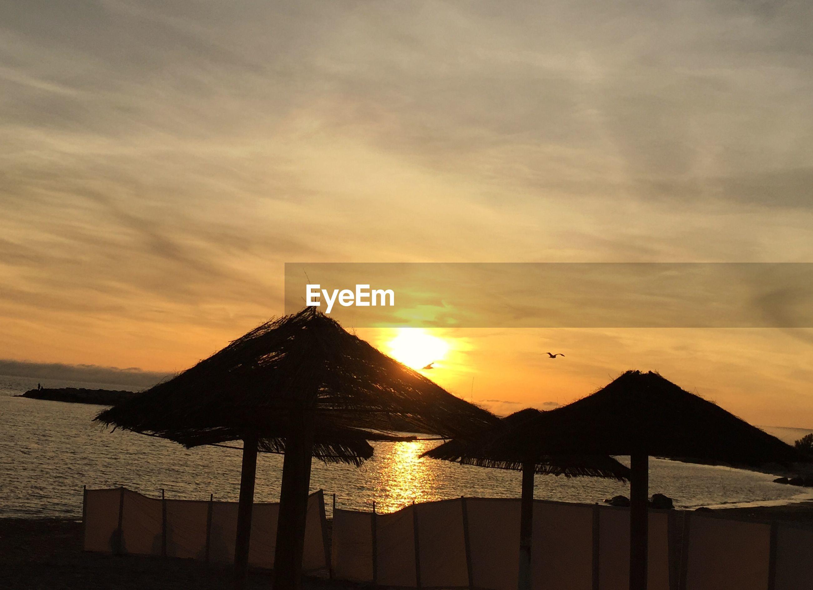 Sunshades on beach against sky at sunset