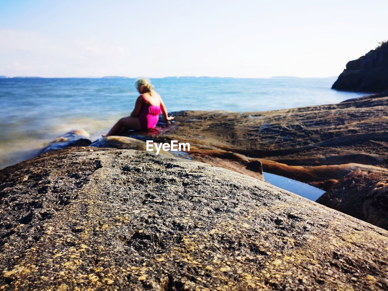 water, sea, rock, sky, rock - object, solid, real people, beauty in nature, lifestyles, leisure activity, nature, beach, one person, sitting, land, horizon, scenics - nature, day, women, horizon over water, outdoors