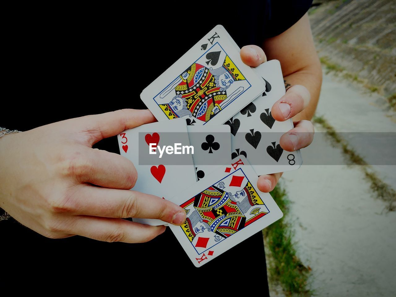 cards, gambling, human hand, playing, holding, leisure activity, leisure games, one person, table, luck, chance, human body part, poker - card game, close-up, real people, outdoors, gambling chip, day