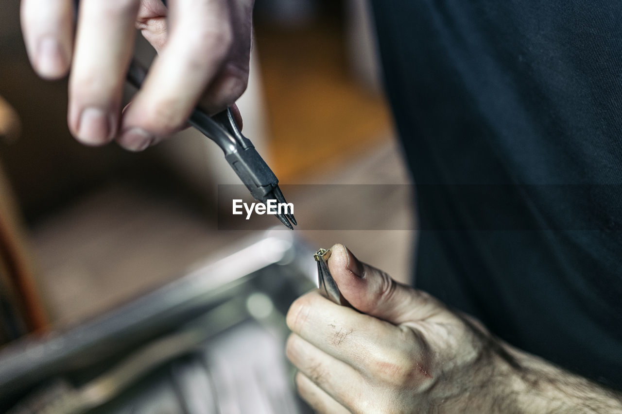 MIDSECTION OF MAN WORKING ON METAL IN KITCHEN