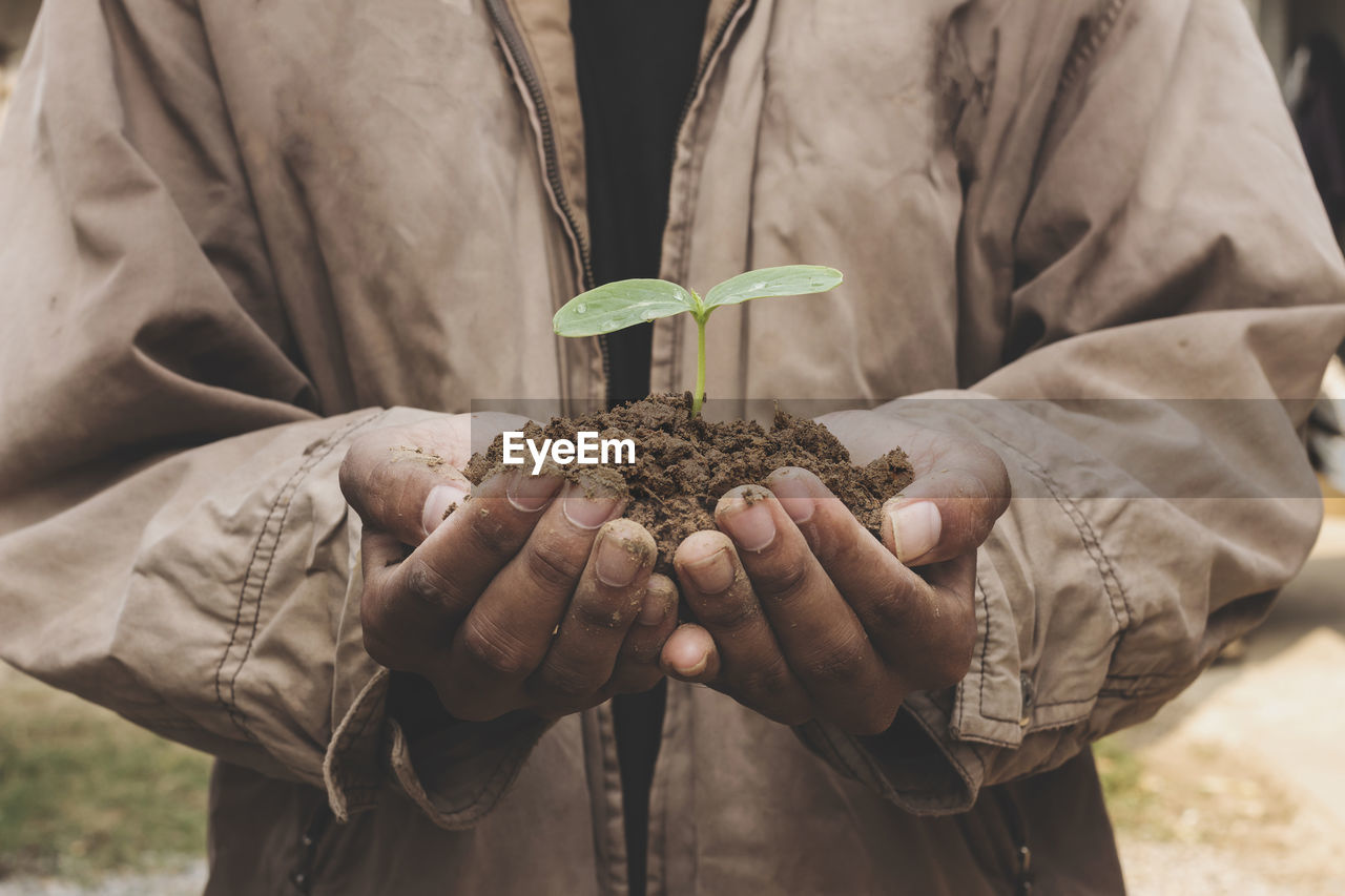 hand, human hand, holding, plant, plant part, leaf, nature, growth, real people, dirt, focus on foreground, human body part, one person, close-up, lifestyles, seedling, hands cupped, green color, beauty in nature, sapling, outdoors, gardening, care, planting, finger