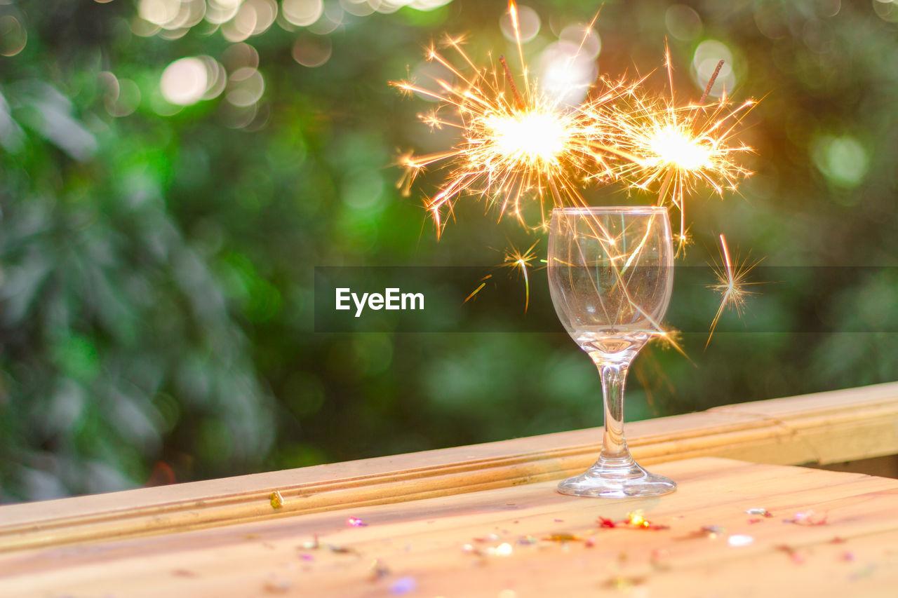 Illuminated sparklers in wineglass on table