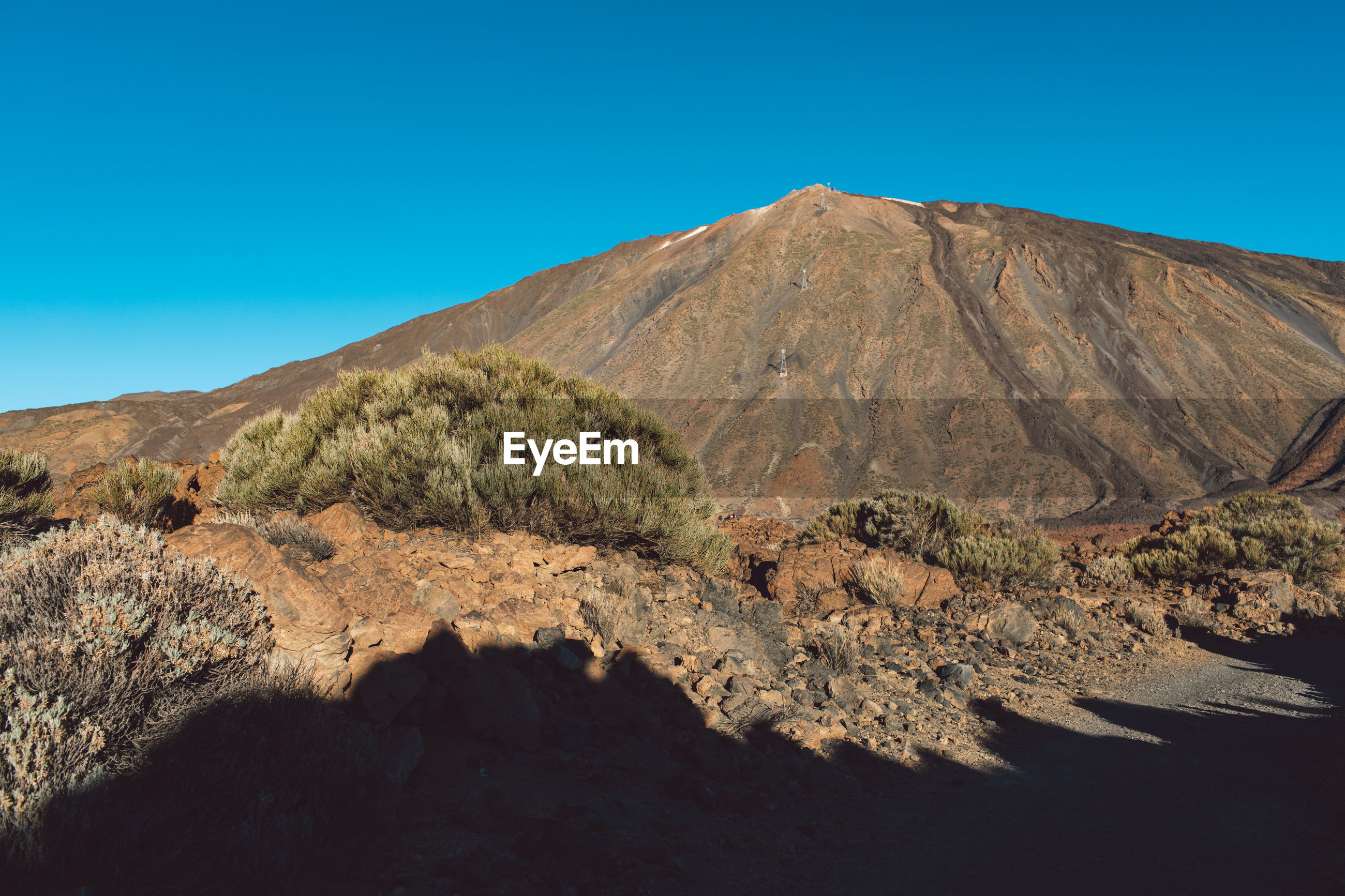 SCENIC VIEW OF VOLCANIC MOUNTAIN AGAINST BLUE SKY