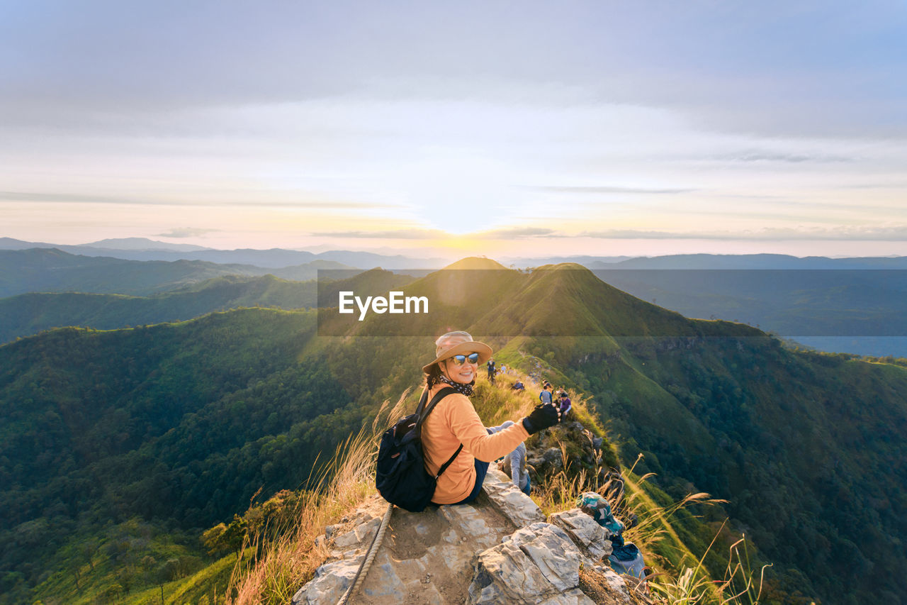 Woman sitting on mountain against sky