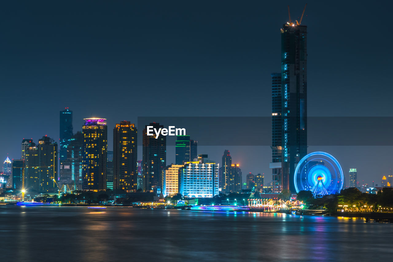 Illuminated Buildings In Front Of Chao Phraya River Against Clear Sky At Night