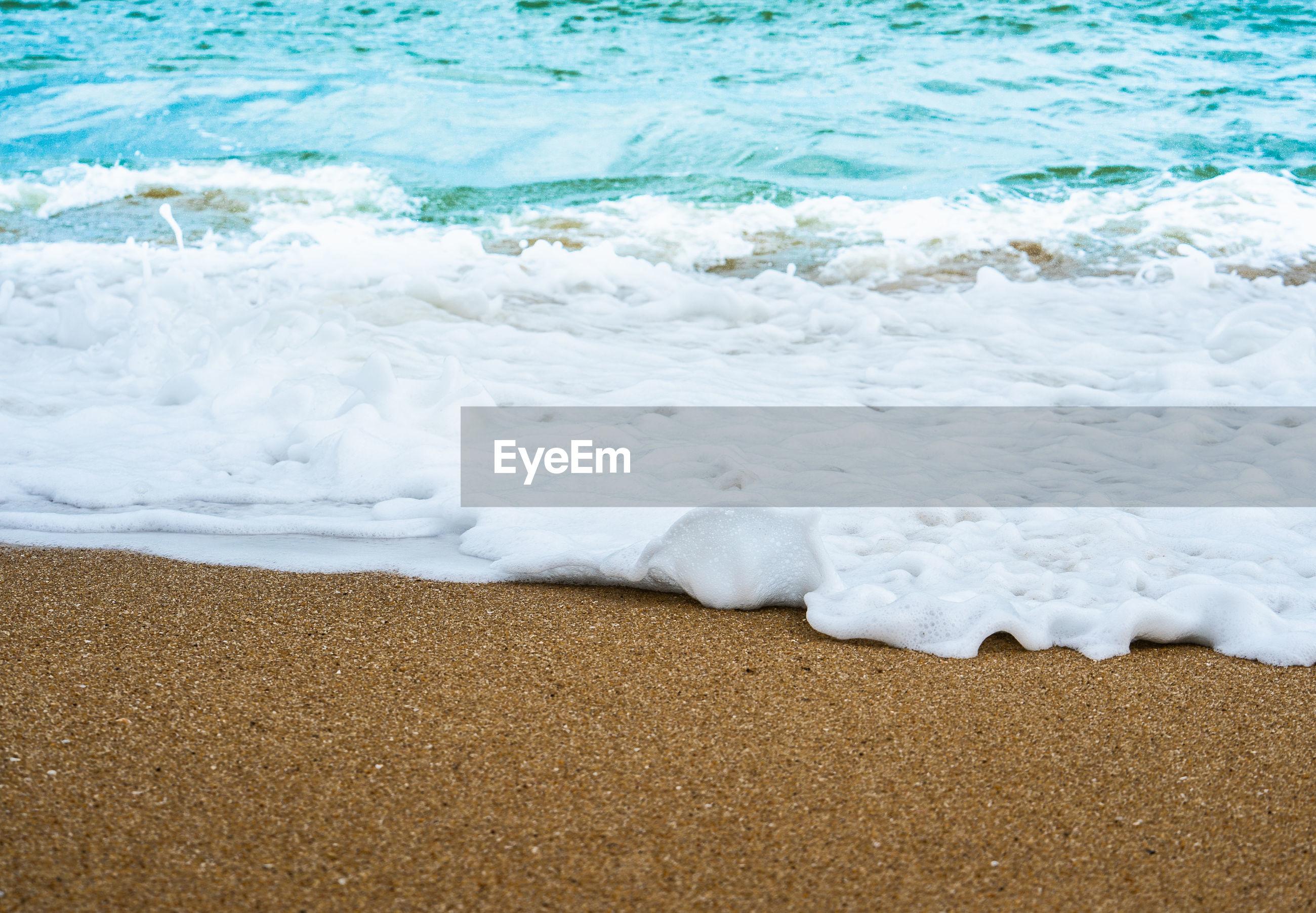 WAVES RUSHING TOWARDS SHORE AT BEACH
