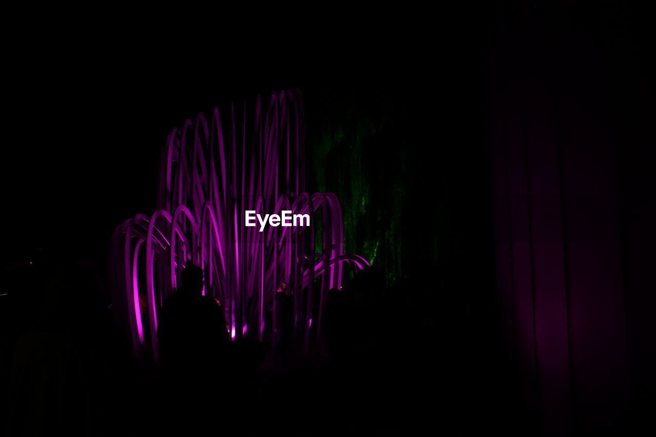 illuminated, dark, indoors, studio shot, motion, pink color, long exposure, black background, night, glowing, one person, light painting, copy space, pattern, lighting equipment, blurred motion, light, real people, light - natural phenomenon, multi colored, nightlife, purple