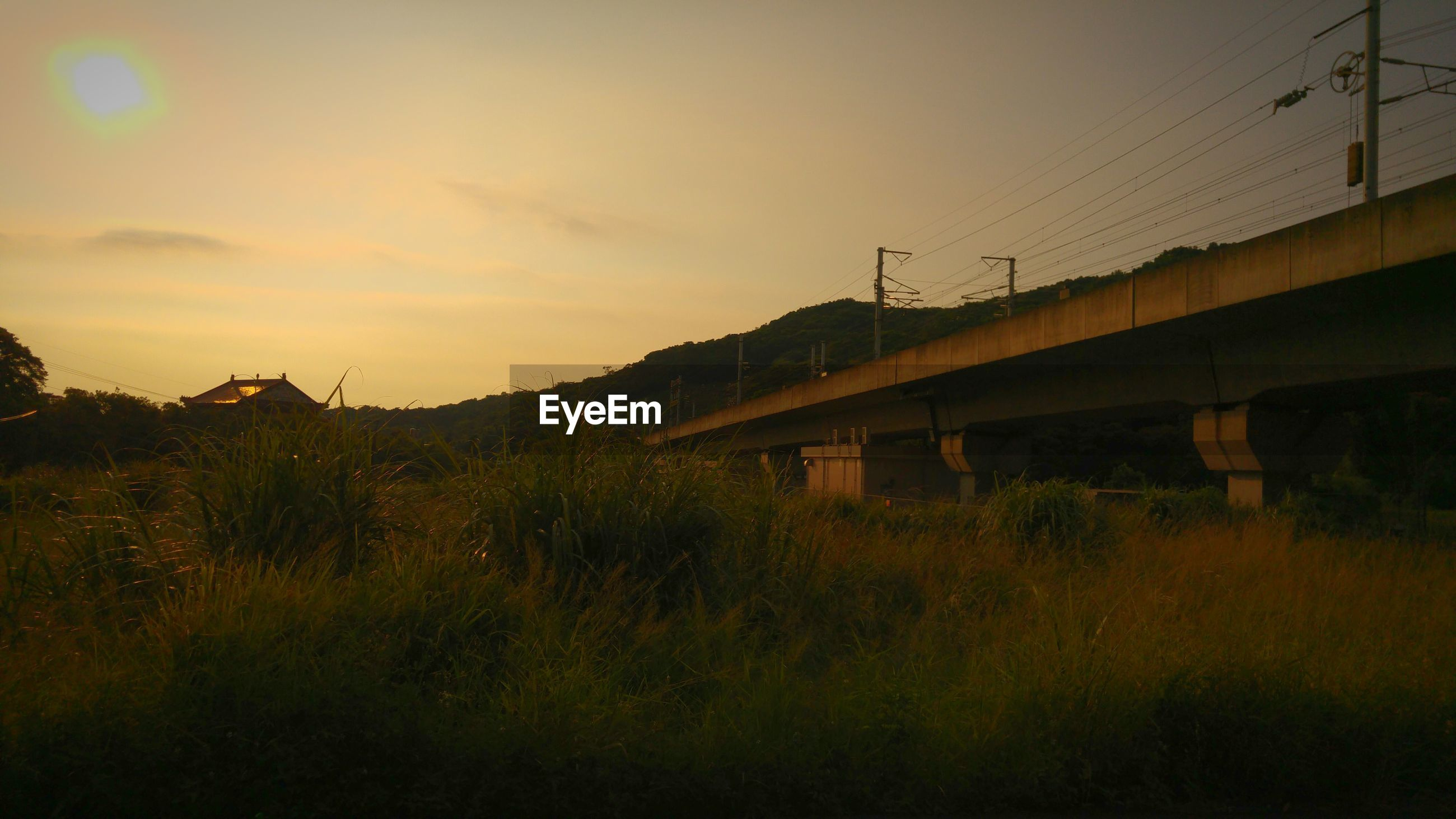 Low angle view of bridge by field against sky during sunset