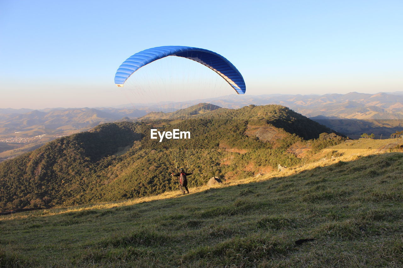 High angle view of man paragliding on grassy mountain