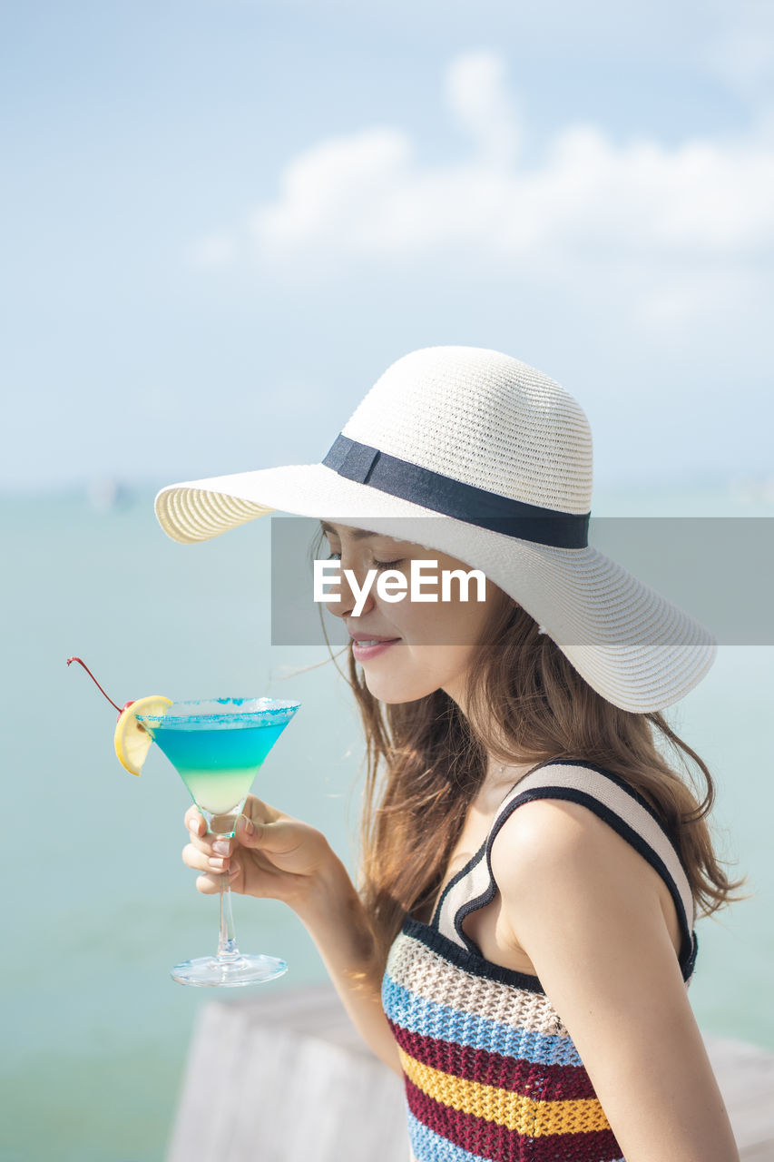 one person, hat, lifestyles, real people, sky, young women, leisure activity, drink, young adult, holding, women, nature, refreshment, day, sunlight, clothing, water, food and drink, cocktail, outdoors, glass, sun hat, drinking, beautiful woman, hairstyle