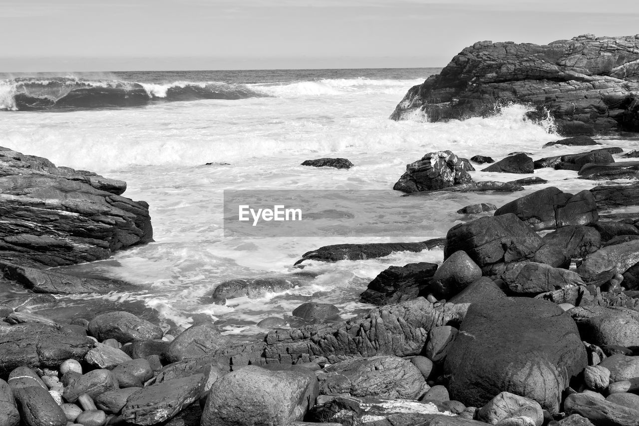 sea, rock, water, solid, rock - object, land, beach, beauty in nature, motion, wave, scenics - nature, nature, horizon over water, surfing, sky, sport, horizon, aquatic sport, day, outdoors, rocky coastline, breaking, power in nature, pebble