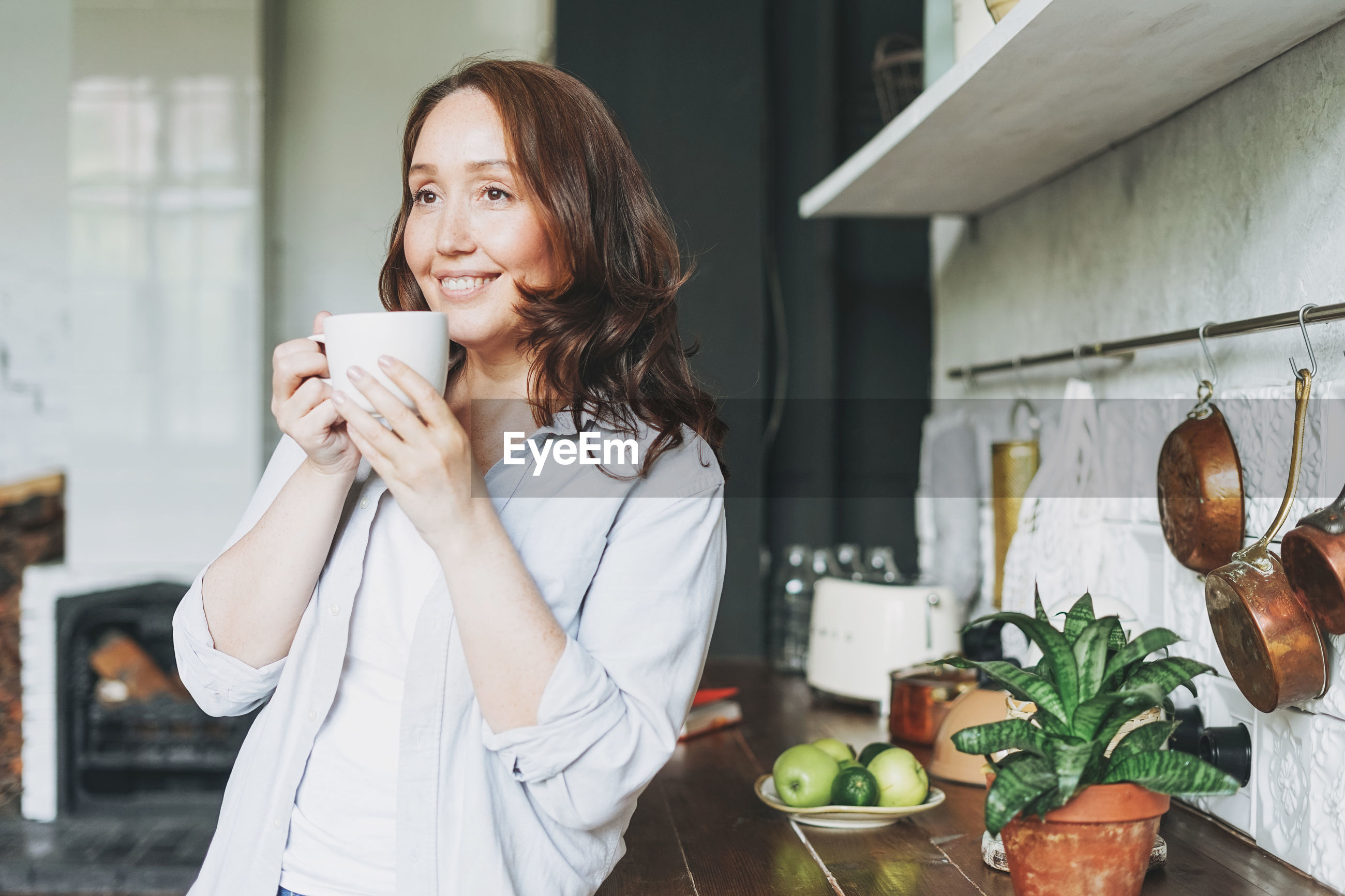 YOUNG WOMAN WITH COFFEE AT HOME