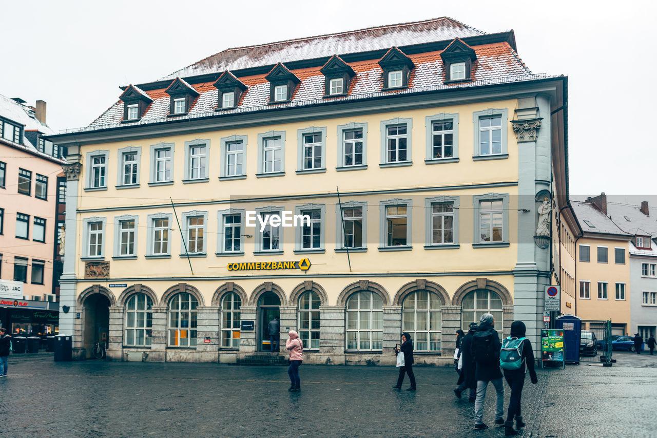 PEOPLE WALKING ON STREET BY BUILDING AGAINST SKY