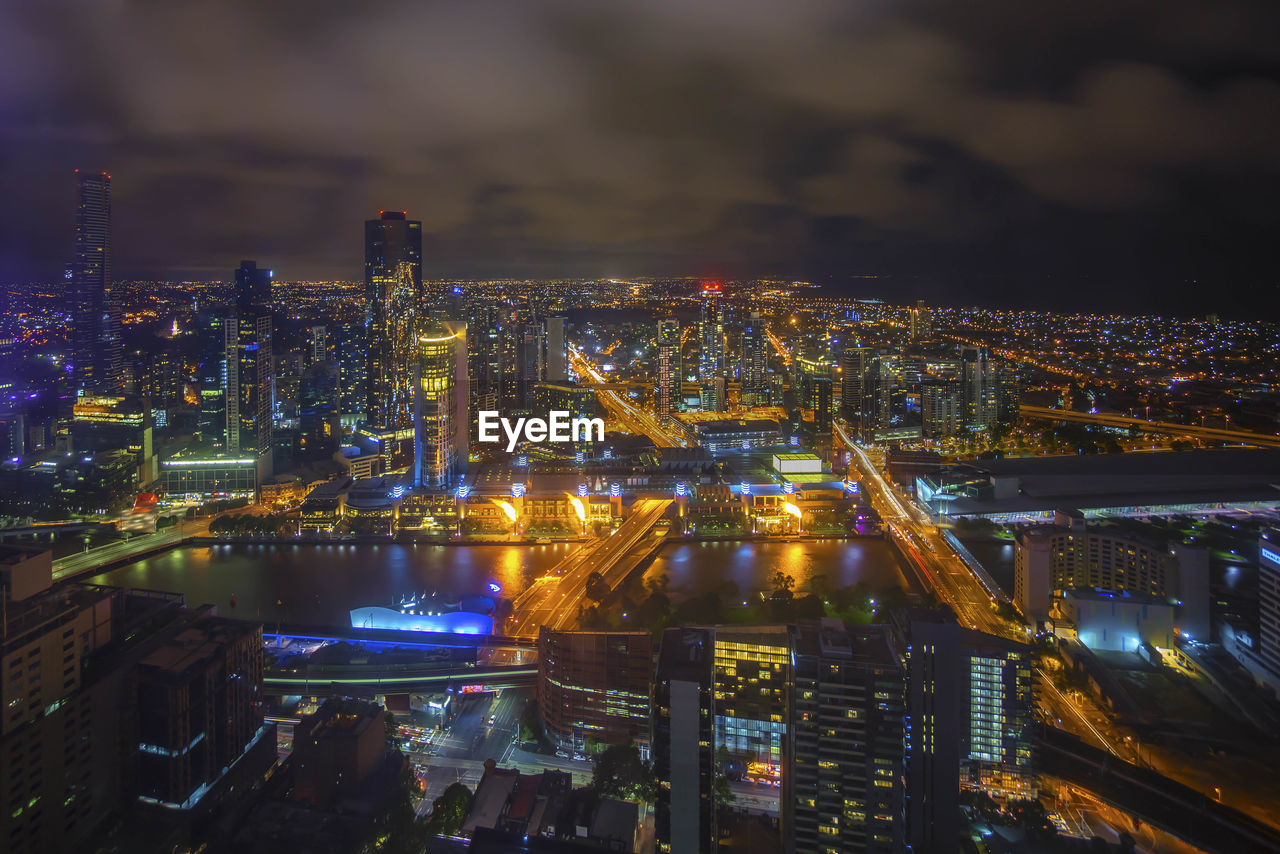 Yarra river in illuminated cityscape against sky at night