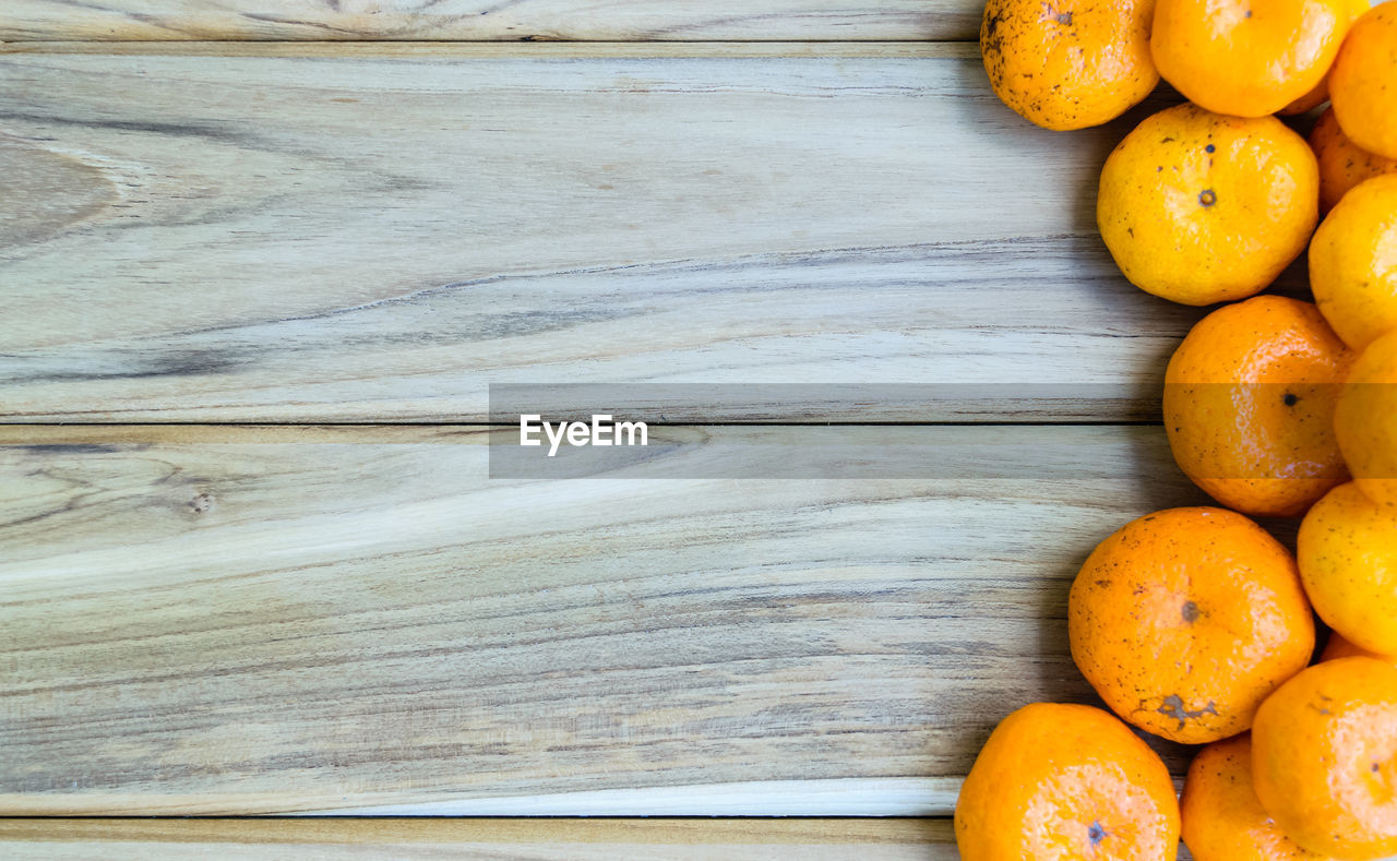 food and drink, food, healthy eating, wellbeing, orange color, freshness, wood - material, fruit, still life, no people, citrus fruit, directly above, table, close-up, high angle view, orange, orange - fruit, indoors, large group of objects, day