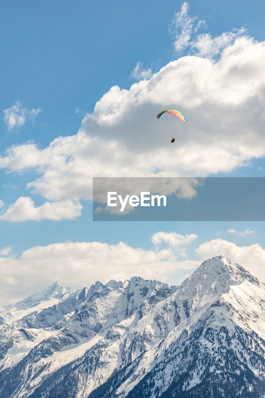 adventure, mountain, extreme sports, sport, cloud - sky, sky, beauty in nature, scenics - nature, parachute, snow, winter, cold temperature, paragliding, leisure activity, mid-air, flying, unrecognizable person, day, nature, mountain range, snowcapped mountain, outdoors
