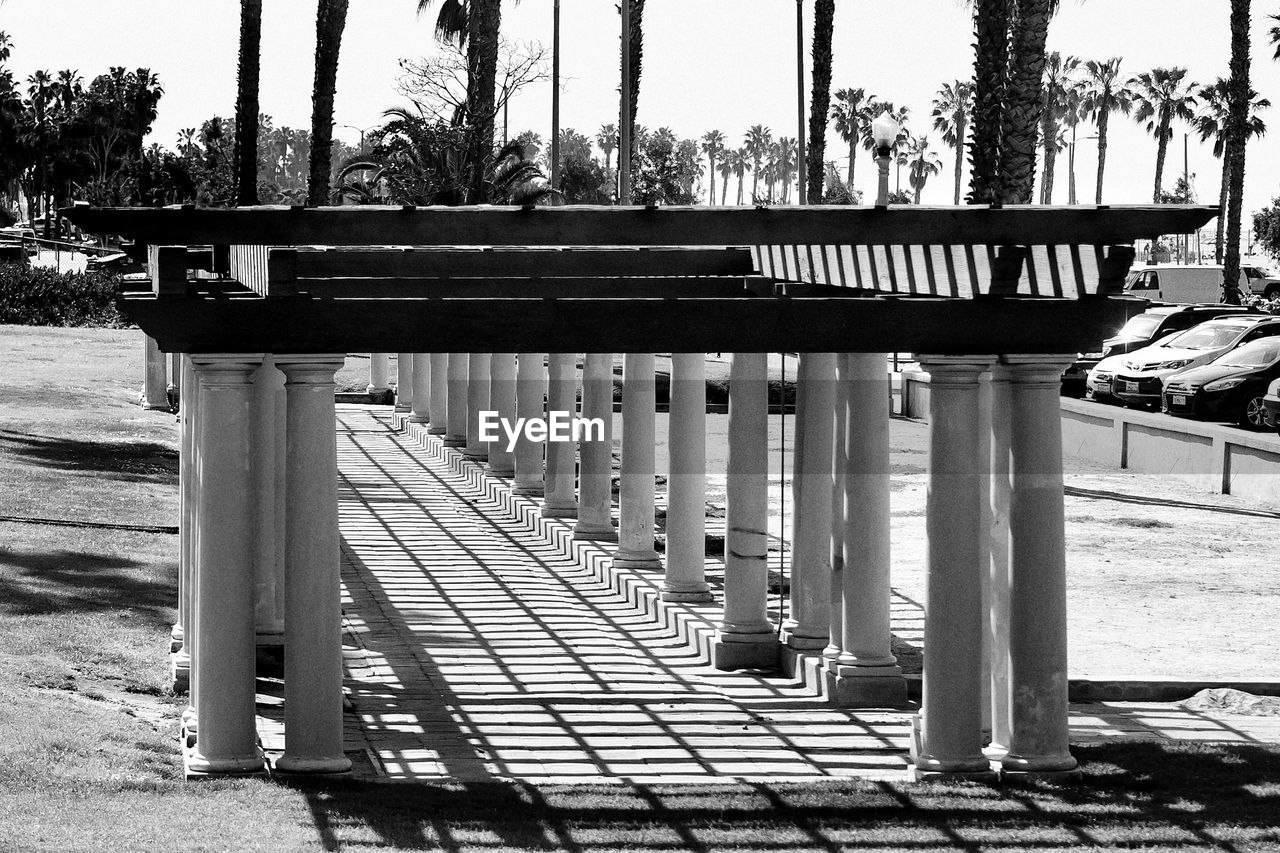 nature, sunlight, day, no people, architecture, footpath, built structure, park, outdoors, in a row, water, shadow, sky, park - man made space, tree, railing, wood - material, transportation, architectural column, paving stone