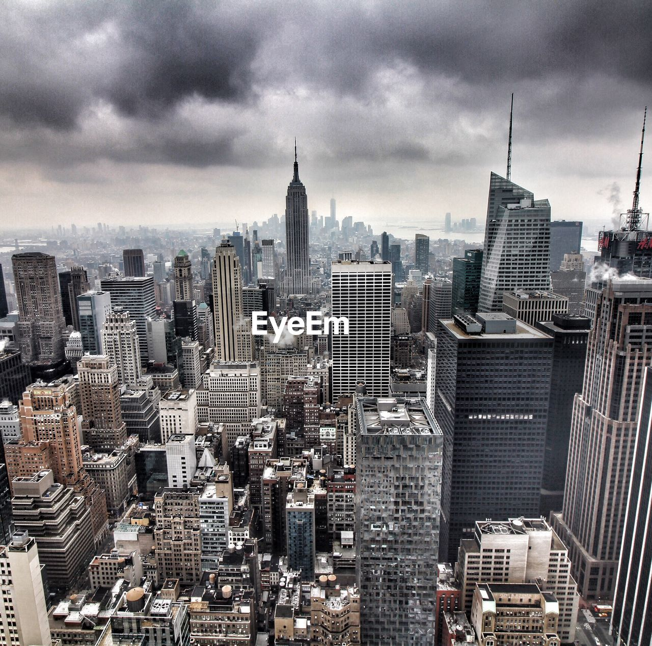 Aerial View Of Modern Buildings In Manhattan Against Cloudy Sky