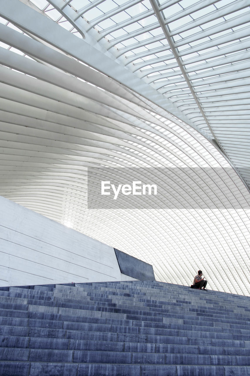 LOW ANGLE VIEW OF MAN ON MODERN OFFICE BUILDING