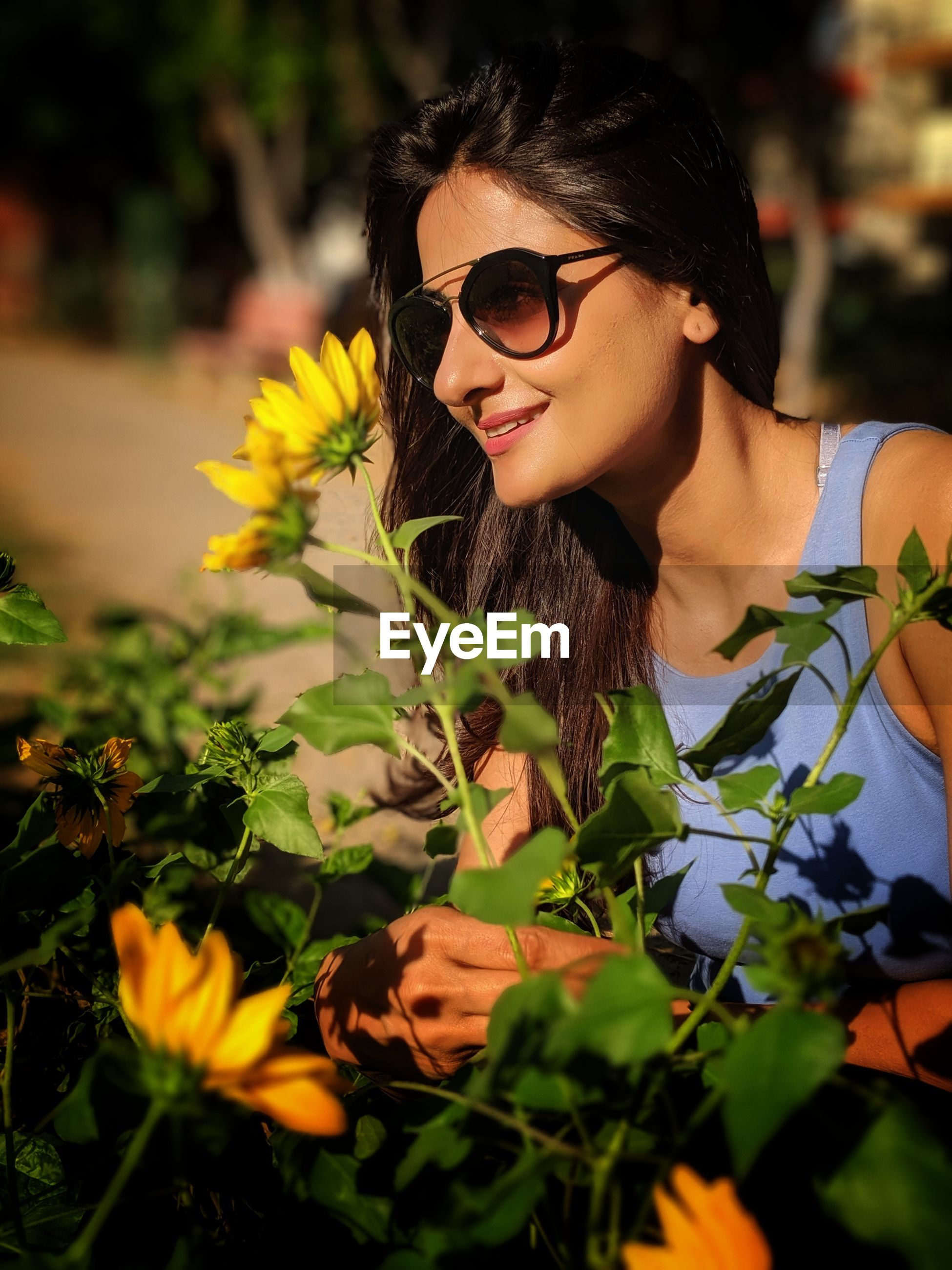 Smiling young woman wearing sunglasses by plants
