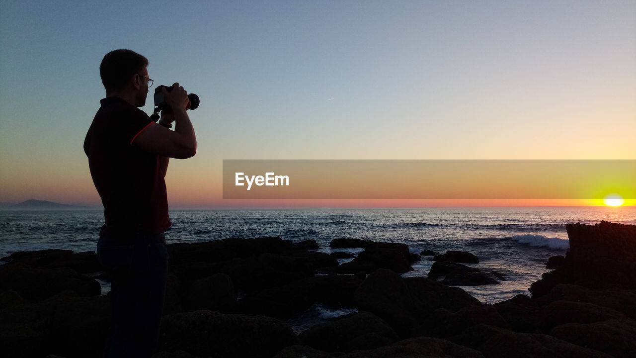 Side View Of Man Photographing Sea Through Digital Camera At Sunset