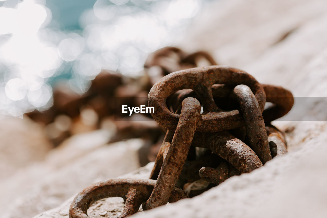 CLOSE-UP OF RUSTY METAL CHAIN OUTDOORS