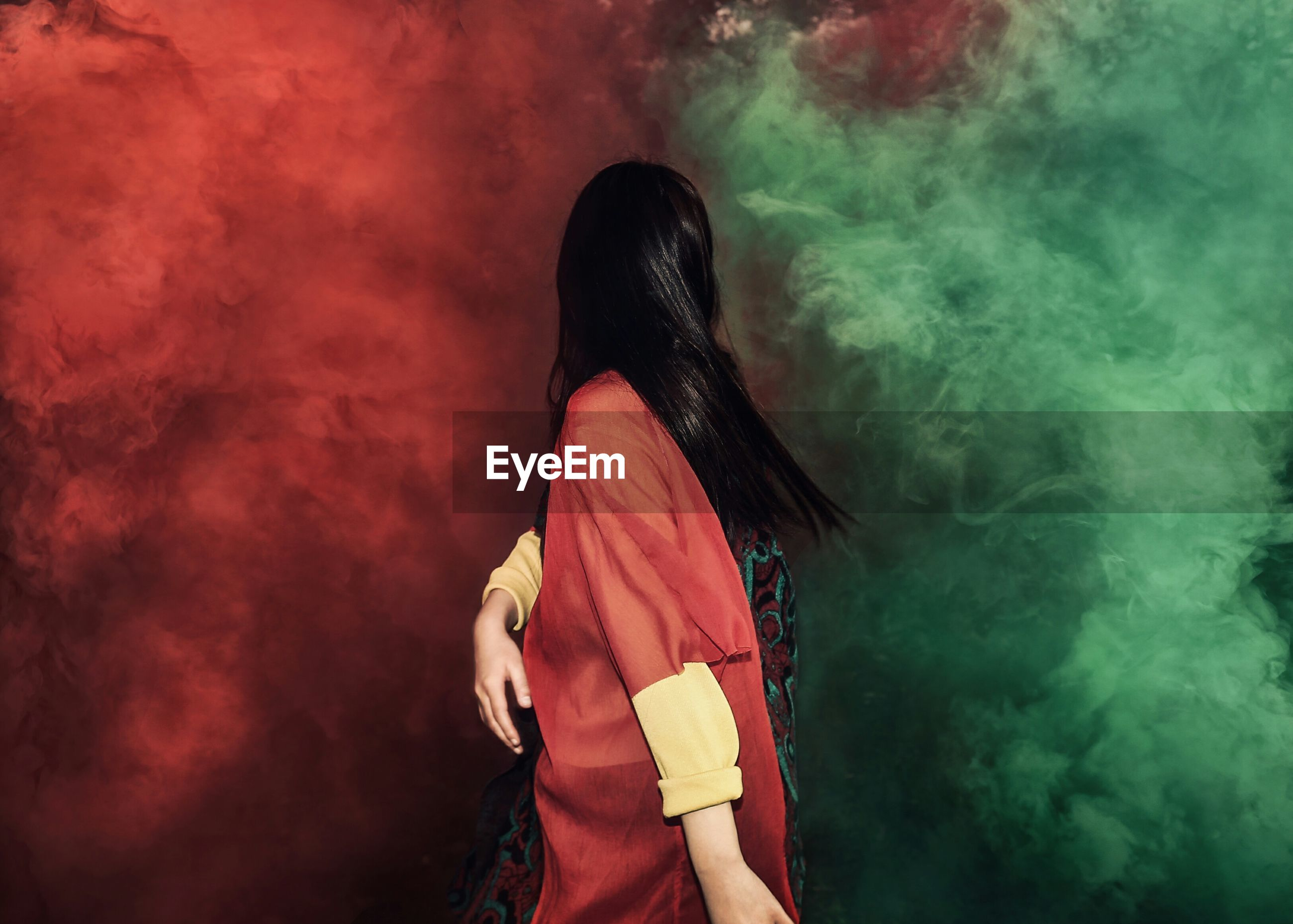 Woman looking at multi colored smoke