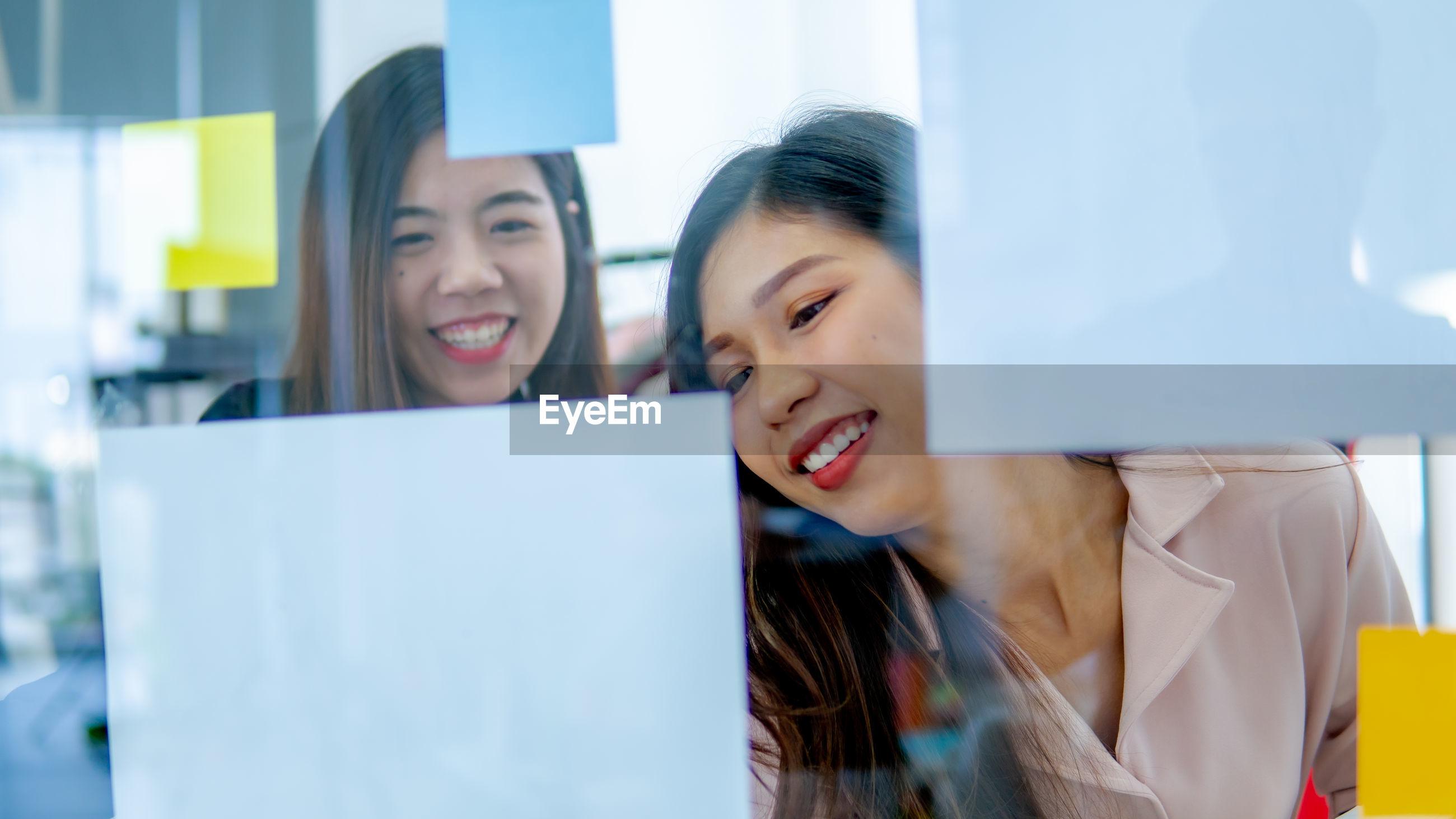 Smiling women working seen through glass