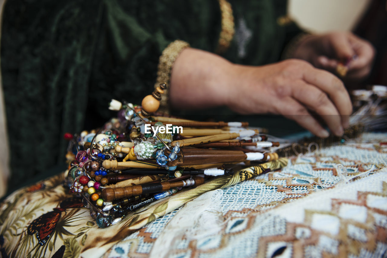 Midsection of woman with jewelry on table