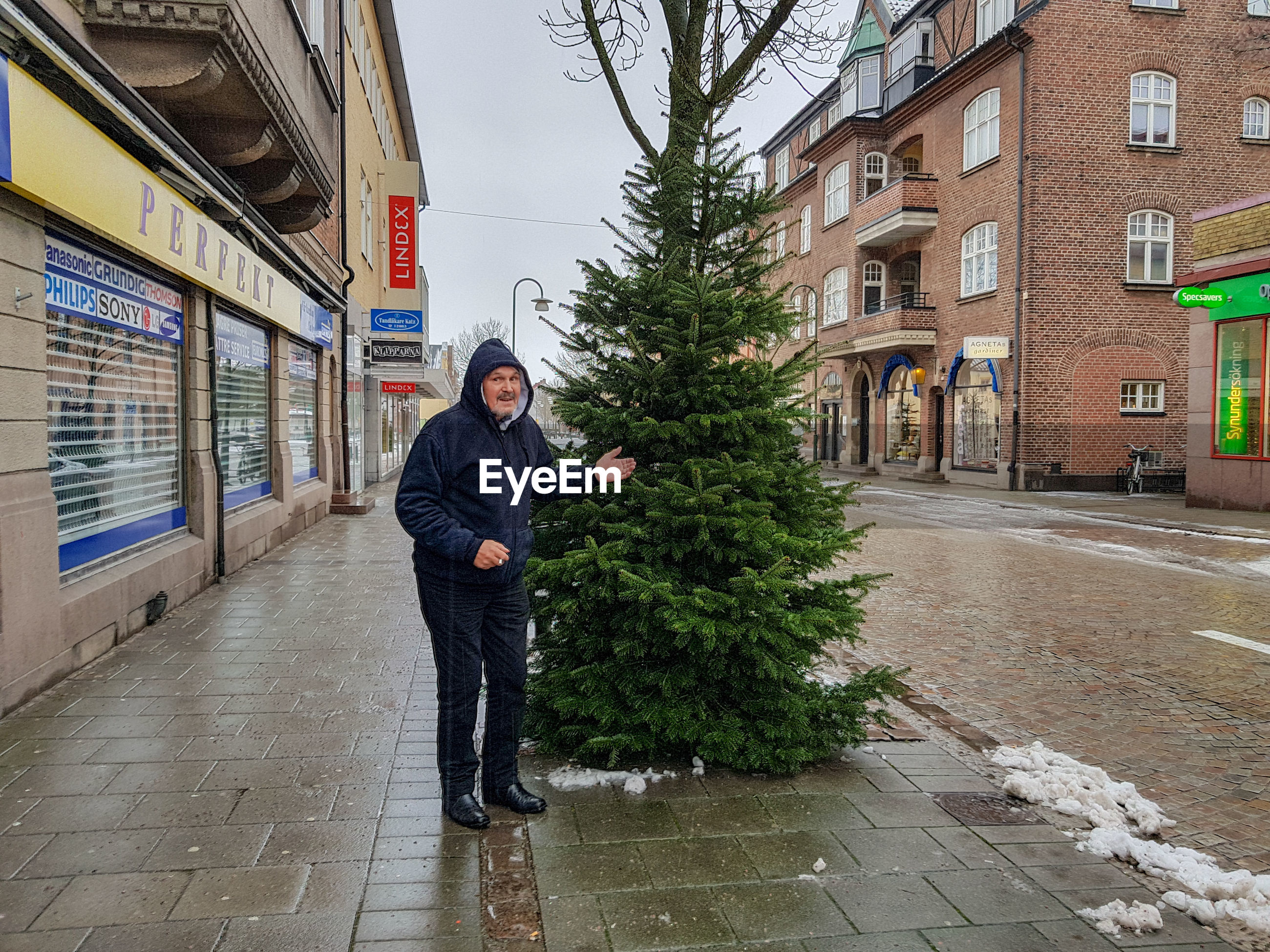 Portrait of man standing by tree in city