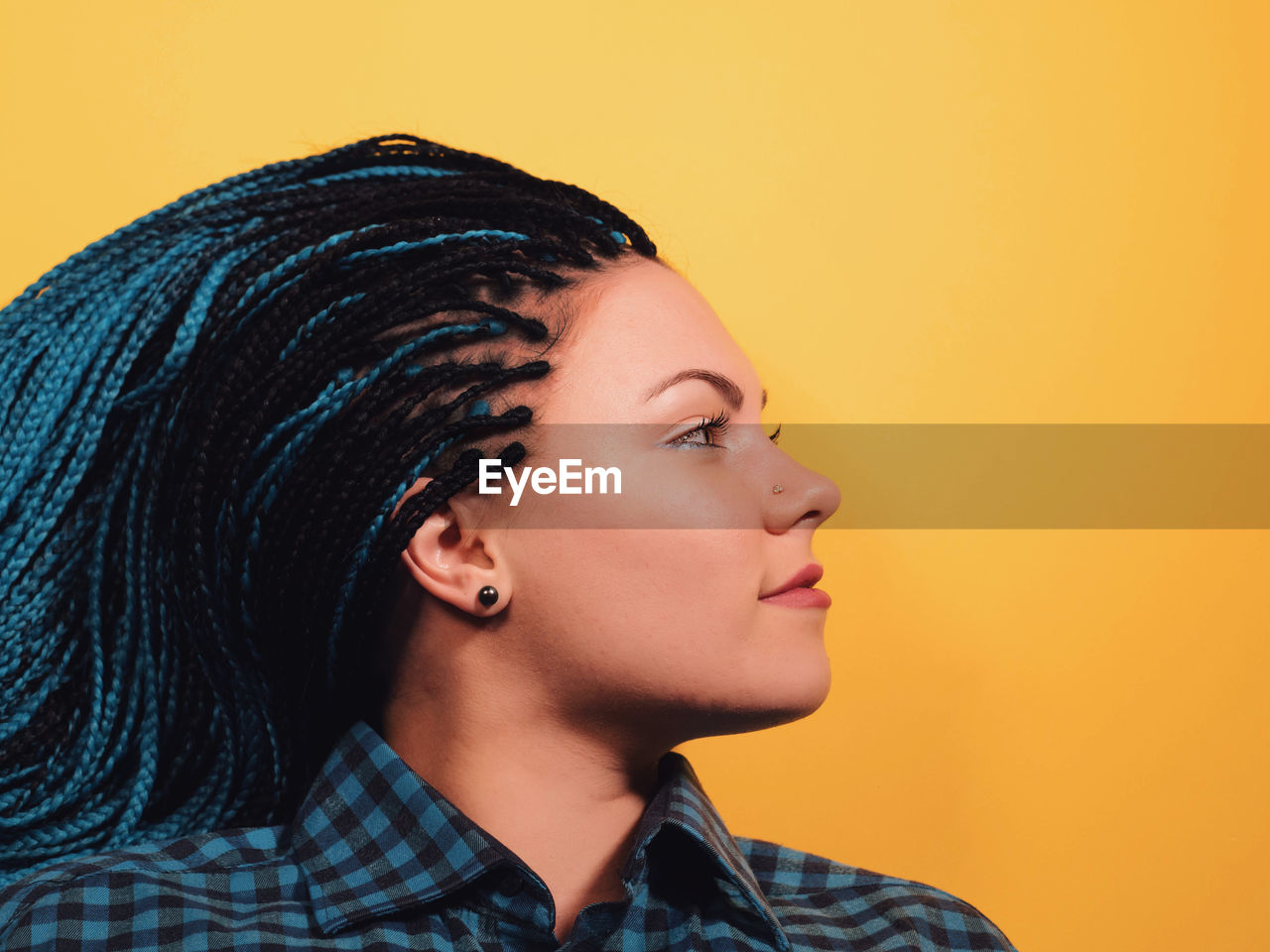Close-Up Of Young Woman With Braided Hair Against Yellow Background