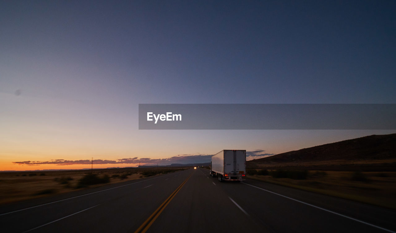 sky, transportation, road, copy space, direction, clear sky, the way forward, nature, sunset, sign, symbol, road marking, diminishing perspective, marking, land vehicle, mode of transportation, truck, highway, no people, vanishing point, outdoors, dividing line