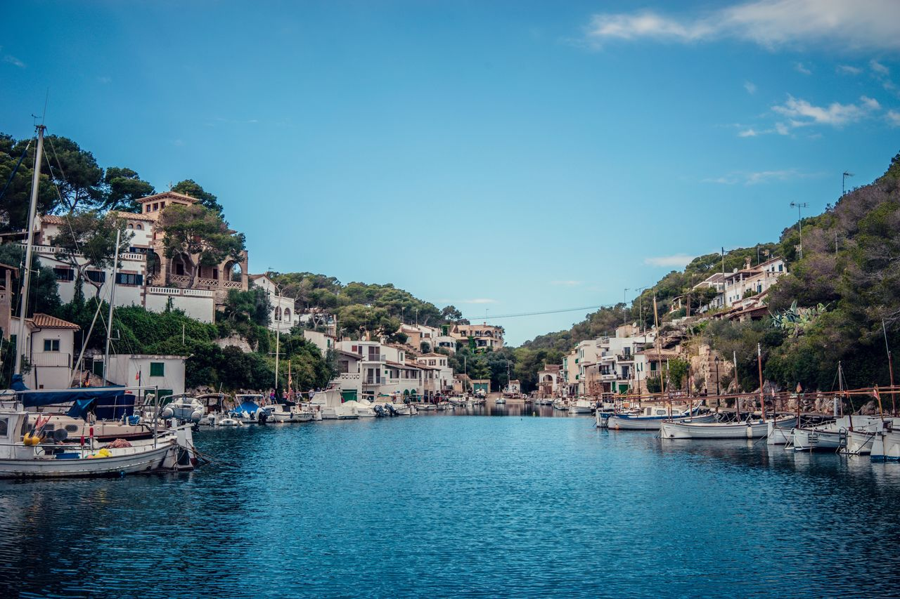 water, building exterior, architecture, built structure, city, building, waterfront, sky, residential district, transportation, nature, nautical vessel, sea, mode of transportation, day, incidental people, town, tree, mountain, outdoors, townscape, place