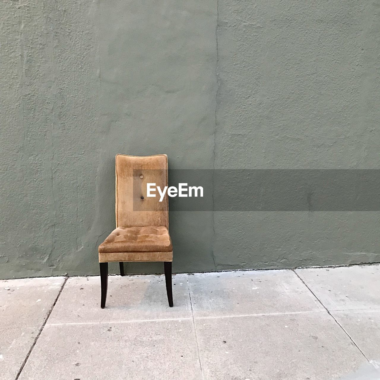 EMPTY CHAIR AGAINST WALL AND FOOTPATH