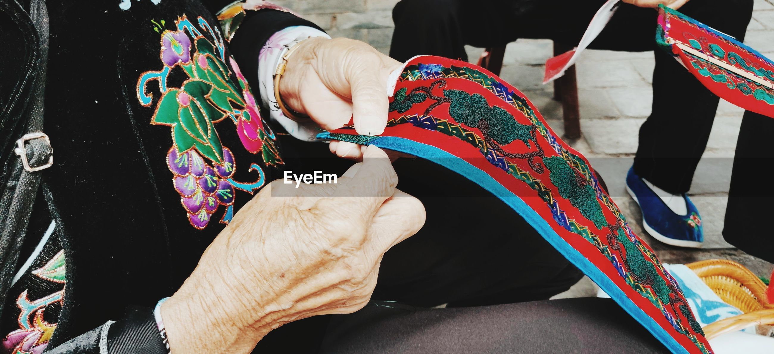 Midsection of man and holding sewing colorful textile