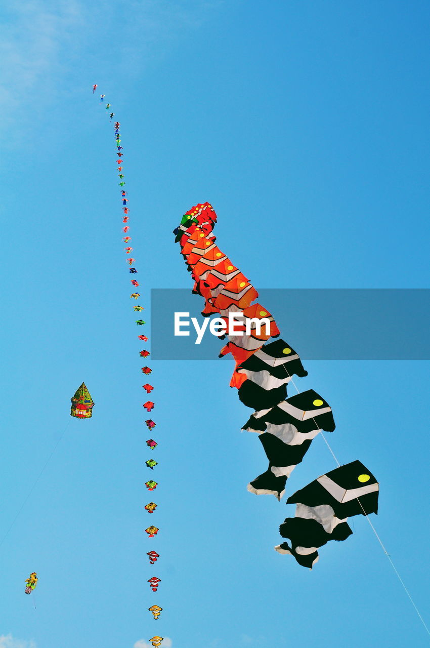 sky, low angle view, multi colored, clear sky, nature, blue, celebration, decoration, no people, day, art and craft, in a row, hanging, creativity, flying, copy space, outdoors, representation, wind, festival