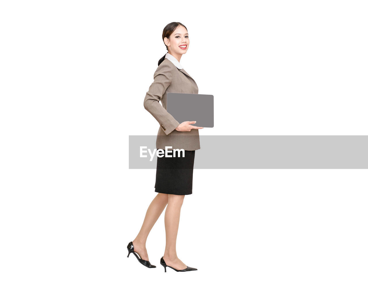 Full length portrait of businesswoman standing with laptop against white background