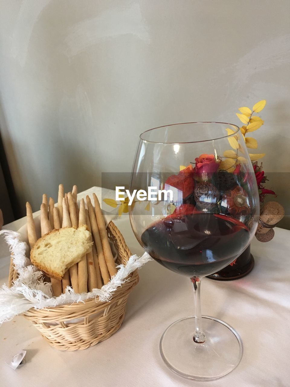 Close-up of red wine by bread on table